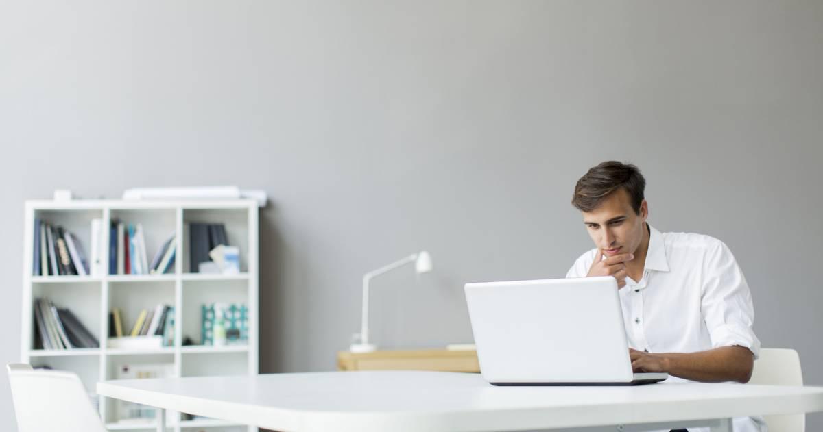 Man werkt thuis met laptop aan tafel